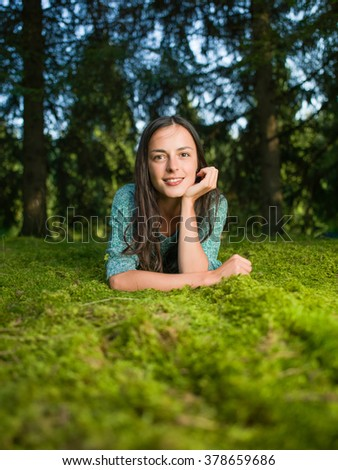 beautiful young woman lies down on the grass smiling with woods in the background