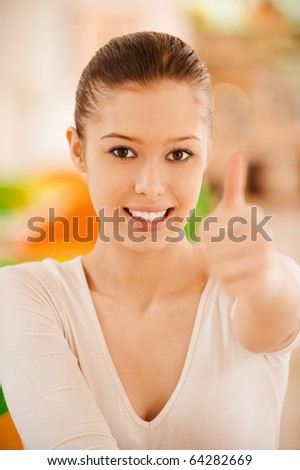 Beautiful young woman lifts thumb meaning that all perfectly. - stock photo