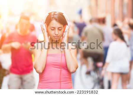 Beautiful Young Woman Listening Music in the City - stock photo
