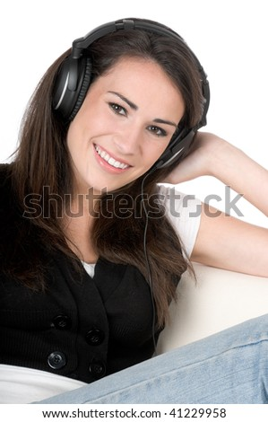 Beautiful young woman listening to music on headphones, happy and smiling, isolated on white background - stock photo
