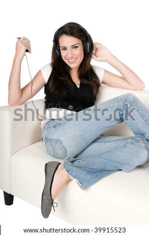 Beautiful young woman listening to music on headphones, sitting on the couch, happy and smiling, isolated on white background - stock photo