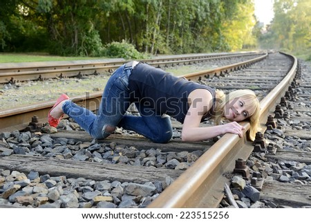 beautiful young woman listening to rail track - stock photo