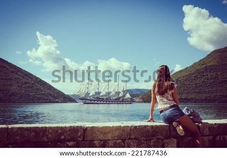 Beautiful young woman looking and waiting for amazing white sailboat at the seacoast. Montenegro, Europe. Toning image. - stock photo