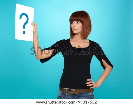 beautiful, young woman looking at a question mark on a white piece of paper, on blue background - stock photo
