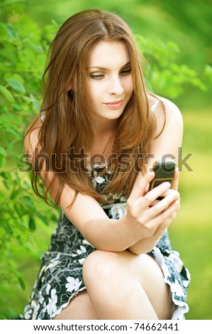 Beautiful young woman looking at mobile phone on green background - stock photo
