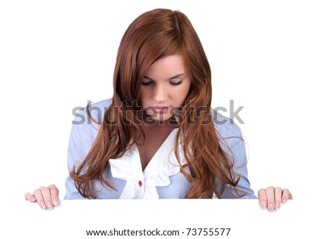 Beautiful young woman looking down to an empty billboard - stock photo