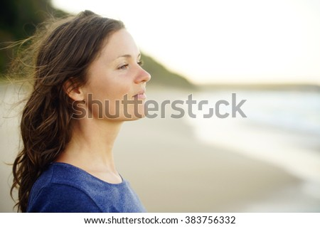 Beautiful young woman looking in the distance, enjoying a moment of quiet happiness and tranquility. - stock photo