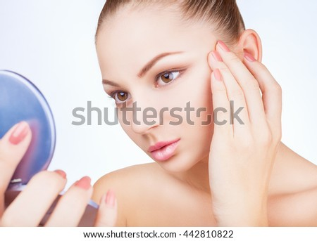 Beautiful young woman looking in the mirror isolated on white background - stock photo