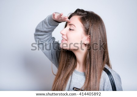 beautiful young woman looking into the distance, close-up isolated on a gray background - stock photo