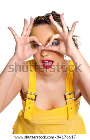 Beautiful young woman looking through imaginary binocular  funny looking through fingers simulating glasses in a yellow dress isolated on a white background