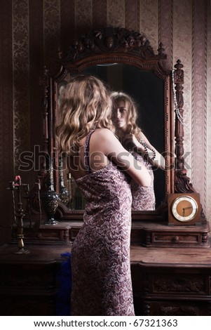 beautiful young woman looks at the reflection in the mirror in the vintage interior