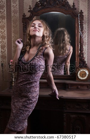 beautiful young woman looks at the reflection in the mirror in the vintage interior - stock photo