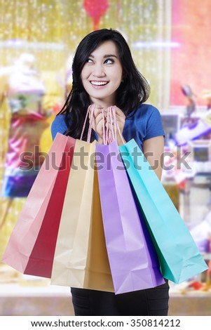 Beautiful young woman looks happy in the shopping center while holding shopping bags - stock photo