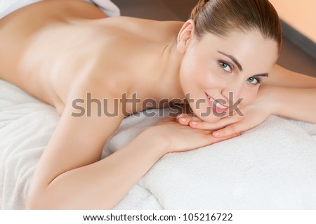 Beautiful young woman lying and relaxing at beauty spa center - stock photo