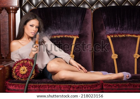 Beautiful young woman lying and smoking hookah. seductive and sexy girl smoking and touching legs - stock photo