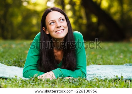 Beautiful young woman lying down in nature and thinking about something,Leisure time - stock photo