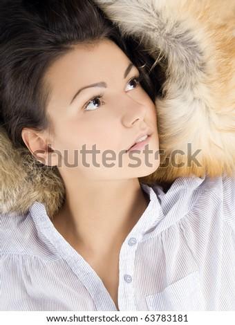 beautiful young woman lying in a fur - stock photo