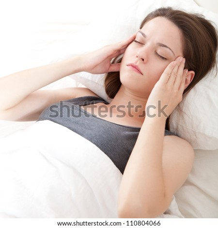 Beautiful young woman lying in bed and having migraine - stock photo