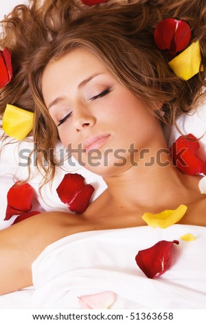 Beautiful young woman lying in rose petals, face closeup - stock photo