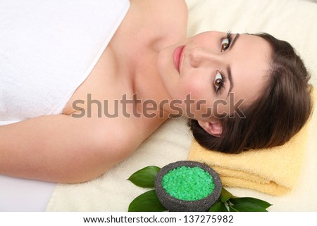 Beautiful young woman lying in spa salon close up