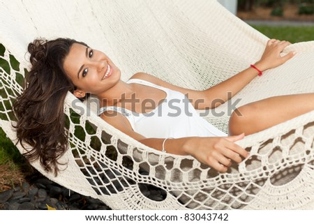 Beautiful young woman lying on a hammock in a trendy South Beach hotel in Miami. - stock photo