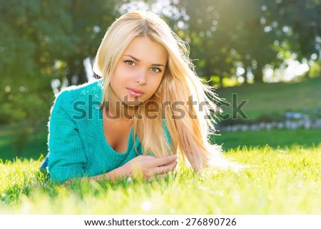 Beautiful Young Woman Lying on Green Grass outdoor. Park. Meadow. Summer. Youth concept - stock photo