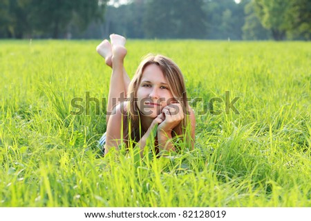 Beautiful young woman lying on green grass. Relaxation - stock photo