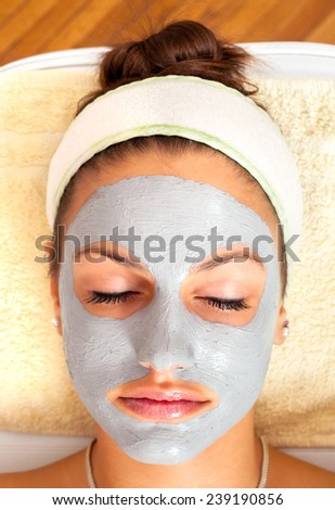 Beautiful young woman lying on massage table with natural facial mask on her face. - stock photo