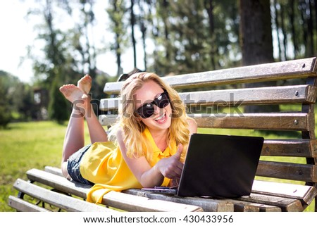 Beautiful Young Woman  lying on the bench at park outdoor Outdoors. Enjoy Nature. Healthy Smiling Girl   working with a laptop. Woman talks on Skype - stock photo