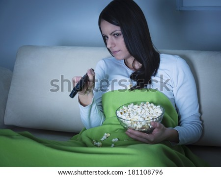 Beautiful young woman lying on the couch and watching TV - stock photo