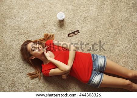 Beautiful young woman lying on the floor - stock photo