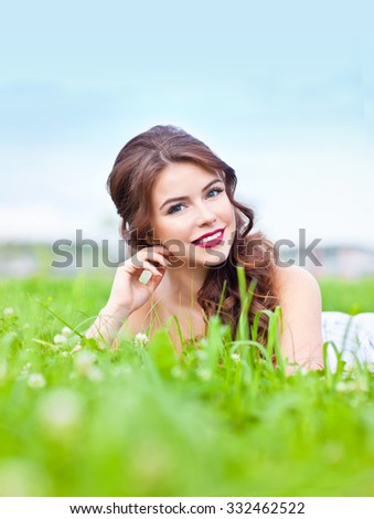 Beautiful young woman lying on the grass and smiling - stock photo
