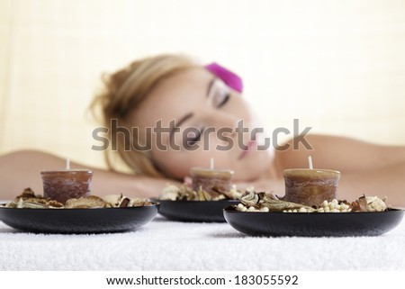 Beautiful young woman lying relaxed with scented candles in SPA aroma terapy - stock photo