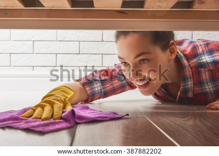 Beautiful young woman makes cleaning the house. Girl rubs dust. - stock photo