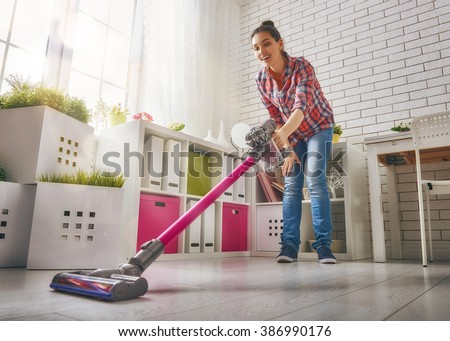Beautiful young woman makes cleaning the house. Woman vacuums the floor - stock photo