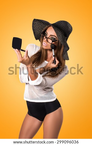 Beautiful young woman makes herself makeup. Isolated on yellow background - stock photo