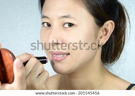 beautiful young woman makes makeup applying pink lipstick on lips with mirror - stock photo
