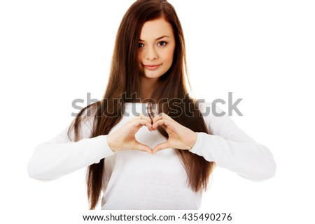 Beautiful young woman making a heart symbol with her hands