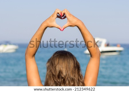 Beautiful young woman making a heart with hands on beach - stock photo