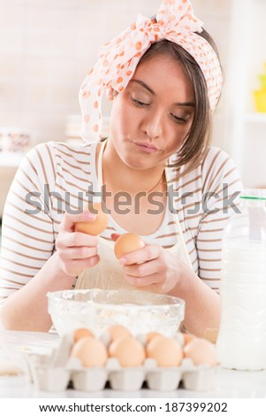 Beautiful young woman making dough in the kitchen. She is breaking eggs. - stock photo