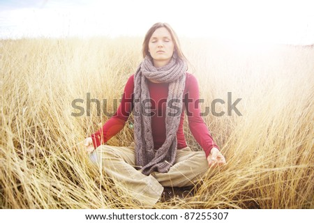 Beautiful young woman meditating in a open field in the long autumn grass - stock photo