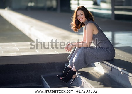 Beautiful young woman, model of fashion, sitting in urban background. Girl smiling.