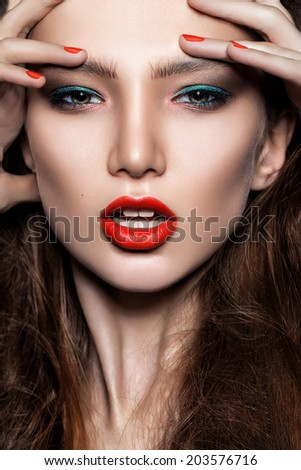 beautiful young woman model with red lips, colorful trendy smoky eyes, perfect skin, red nails. Trendy evening make-up - stock photo