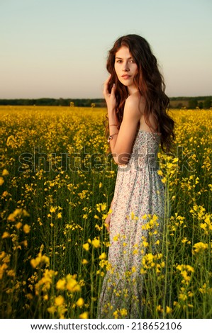 beautiful young woman moving and posing in the rapeseed field, retro filter photo effect - stock photo