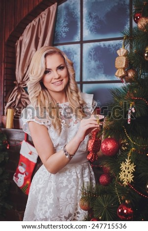 Beautiful young woman near a Christmas tree with gifts
