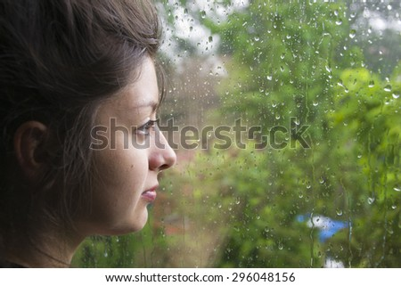 beautiful young woman of Asian appearance looks out the window as the rain falls. The window in rain drops with green trees as background. Sadness and search. The girl has big black eyes.