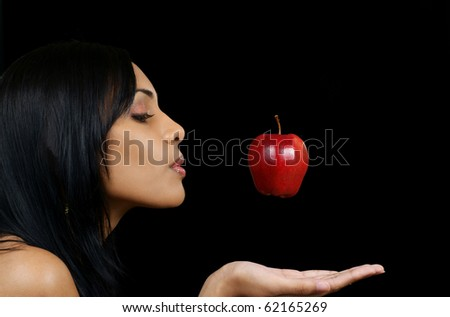 beautiful young woman of east Indian ancestry catching an apple in midair - stock photo