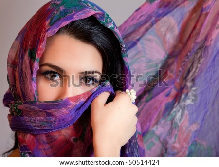 Beautiful young woman of multiple ethnicity in a glamour/fashion pose with a shawl partially covering her face on a gray background.