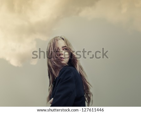 beautiful young woman on a background of clouds - stock photo