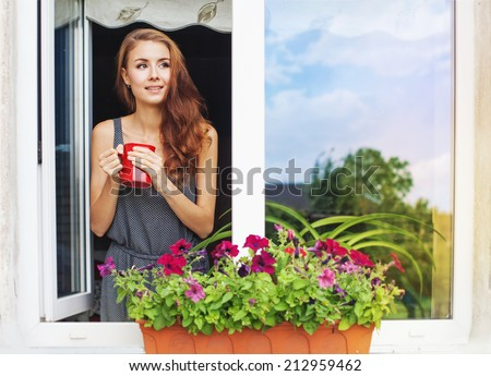 Beautiful young woman on a balcony enjoing morning with cup of coffee - stock photo